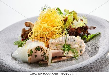 Salad with squid and fried potatoes. Traditional asian recipe with seafood and garnish. Delicious meal with sauce, vegetable and greenery on plate. Oriental cuisine, food composition
