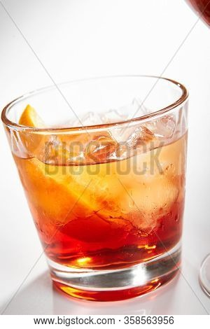 Negroni cocktail close up. Alcohol strong aperitif drink in glass side view. Beverage with red vermouth, Campari liqueur, gin, orange and ice in drinkware. Italian cocktail portion in glassware