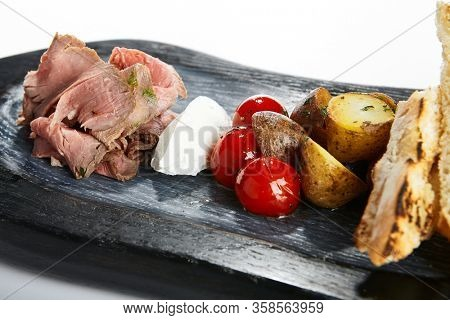 Roast beef with cream cheese and ciabatta. Chopped meat with vegetables on wooden tray closeup view. Meal with cut tomatoes and potatoes. Dish igredients, cooking process. Food composition
