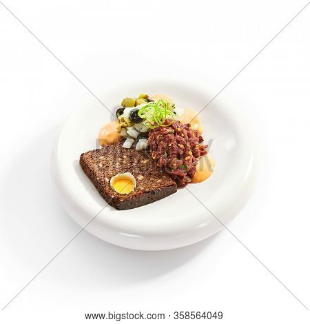 Beef tartare side view. Delicious chopped meat with sauce and bread. Dish with mustard and greenery on plate. Restaurant delicacy, haute cuisine. Food presentation, traditional recipe