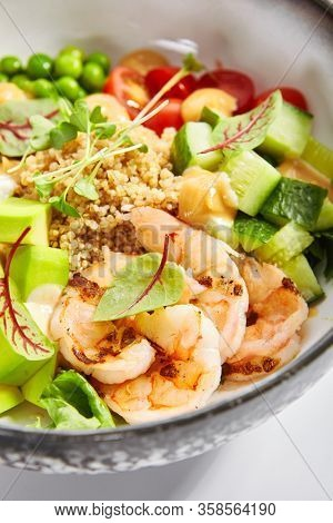 Bowl of couscous with shrimp and vegetables. Tasty meal with tofu cheese and seafood closeup view. Prawn, cut cucumber and tomato. Delicious dish decorated with sauce, pepper and avocado