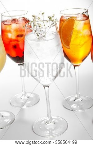 Spritz fruit cocktails. Alcohol soft drinks in glasses side view. Refreshment beverage with coconut, berry, orange in drinkware. Exotic summer beach cocktail portions with crushed ice in glassware