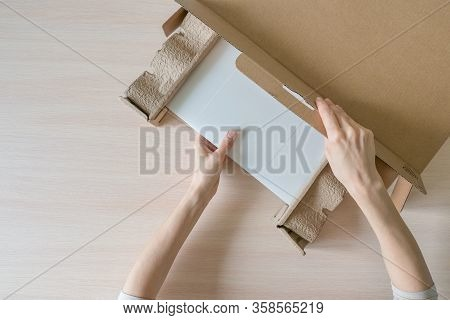 Unpacking A New Laptop From A Cardboard Box. Hands Open The Box. Unpacking The Received Parcel. Top