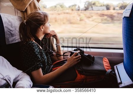 Young Woman Sit Traveling By Train. Sit Alone At Window And Look At It. Female Photographer Has Vaca