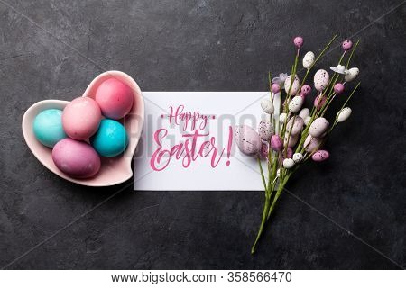 Easter greeting card with colorful easter eggs decor on stone background. Top view flat lay with space for your greetings