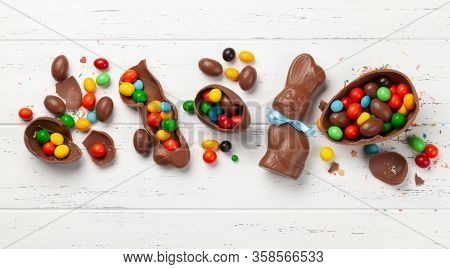 Chocolate easter eggs, choco rabbit and colorful sweets on wooden background greeting card. Top view. Flat lay