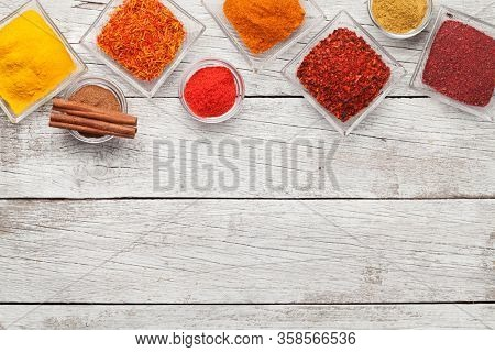 Various spices in bowls on white wooden table. Indian cuisine. Top view flat lay with copy space