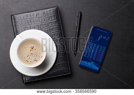 Office leather desk table with coffee cup, notepad, smartphone with stock market charts. Top view flat lay