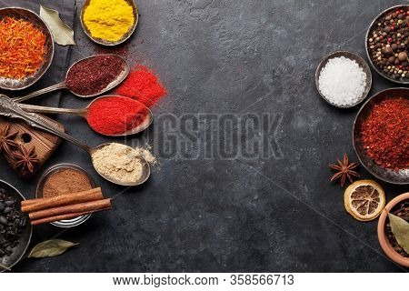 Various spices in bowls and spoons on dark stone table. Indian cuisine. Top view flat lay with copy space