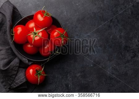 Fresh ripe tomatoes in bowl on stone table. Top view with copy space. Flat lay