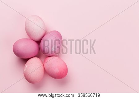 Easter greeting card with colorful easter eggs on pink background. Top view flat lay with space for your greetings