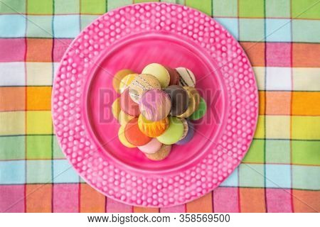 Macarons tower on pink dessert plate top view. Retro pink vintage tablecloth Easter table home kitchen. Assortment of pastel color macaron of different flavors. French pastry macaroons presentation.