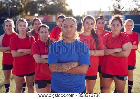 Portrait Of Womens Football Team With Manager Training For Soccer Match On Outdoor Astro Turf Pitch