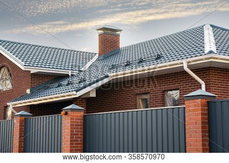 Frame House Under Construction With A Gutter System On A Metal Roof. Brick Chimney Pipe. Automatic M