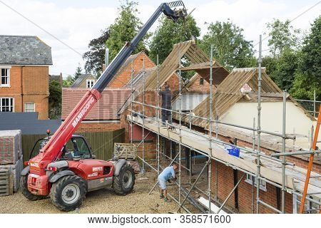 Buckingham, Uk - September 08, 2016. Builders Working With A Telehandler For Demolition And Rebuild