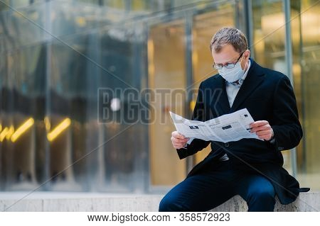 Outdoor Shot Of Serious Man Boss Takes Break After Walking, Reads Newspaper, Wears Spectacles For Go