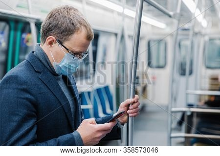 Serious Man Commutes To Work In Underground Wears Virus Protective Mask Being Always In Touch With M