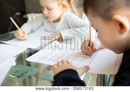 Schoolboy And Schoolgirl Writing Letters. Close-up  Pencil In The Hand Of Child. Children Learning T