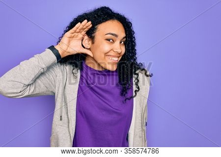 Young african american sporty woman wearing casual sweatshirt over purple background smiling with hand over ear listening an hearing to rumor or gossip. Deafness concept.