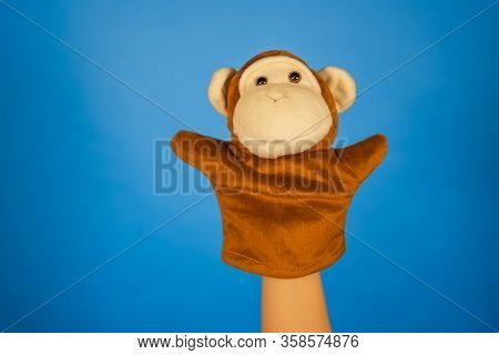 Soft Puppet Toy On Hand On Blue Background. Concept Of Puppet Show. Close-up Of Hand With Puppet Mon