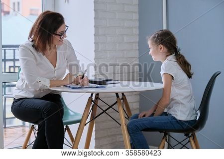 Communication Session Of School Psychologist And Girl 9, 10 Years. Child Tells Psychotherapist His E