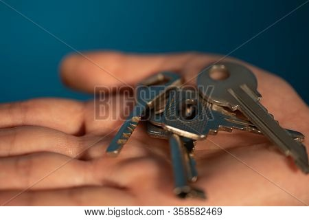 Close-up Of Hand With Different Keys. Huddle Of Keys On Womans Palm On Blue Background.