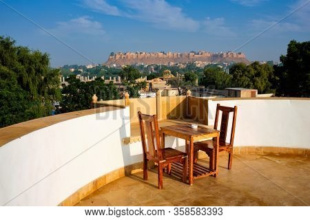 Rooftop Table with chairs with view of tourist landmark of Rajasthan - Jaisalmer Fort known as the Golden Fort Sonar quila, Jaisalmer, Rajasthan, India