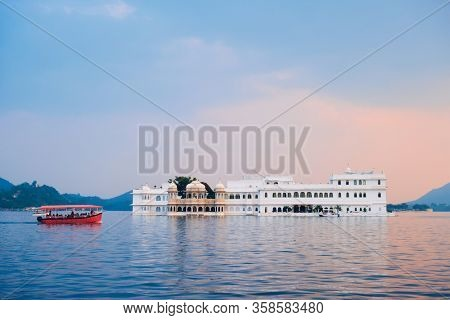Romantic luxury India travel tourism - tourist boat in front of Lake Palace (Jag Niwas) complex on Lake Pichola on sunset with dramatic sky, Udaipur, Rajasthan, India