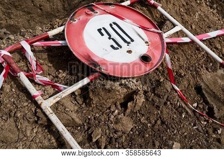the road sign for the speed limit of thirty kilometers or miles per hour and the road fence for performing repair work lies on the ground