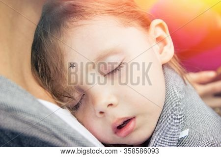 Little Girl Sleeping On Her Mother Chest In Baby Wrap Carrier