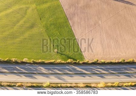 Top Down Aerial View Of Highway Interstate Road With Fast Moving Traffic And Parking Lot With Parked