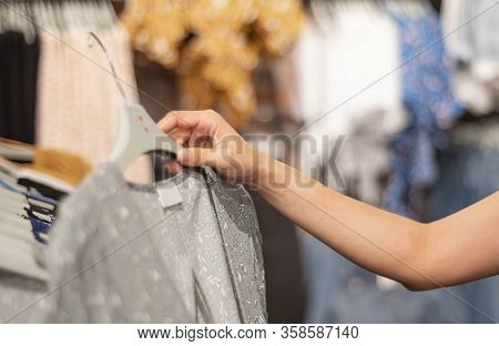 Woman Hand Choosing Clothes For Checked Pattern Cotton Dress On The Rack In Cloth Shop At Department