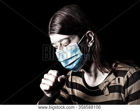 Woman with surgical mask sneezing or coughing. Pandemic or epidemic and scary, fear or danger concept. Protection for biohazard like COVID-19 aka Coronavirus. Black Background