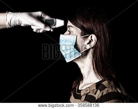 woman having the fever measured or taken with digital thermometer by nurse. Pandemic or epidemic, scary, fear or danger concept. Protection for biohazard like COVID-19 aka Coronavirus.