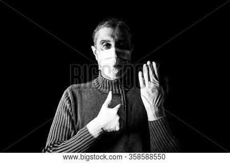 Man with surgical mask, protective gloves and thumbs up. Pandemic or epidemic, scary, fear or danger concept. Protection for biohazard like COVID-19, Coronavirus, Ebola. Black Background. Black White
