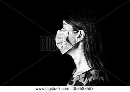 Woman with surgical mask. Pandemic or epidemic and scary, fear or danger concept. Protection for biohazard like COVID-19 aka Coronavirus. Profile portrait. Black Background. Black and White.