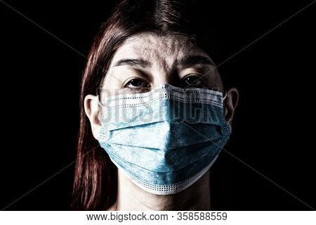 Woman with surgical mask. Pandemic or epidemic and scary, fear or danger concept. Protection for biohazard like COVID-19 aka Coronavirus. Close-up  portrait. Black Background.