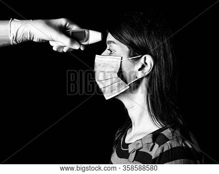 woman having the fever measured or taken with digital thermometer by nurse. Pandemic or epidemic, scary, fear or danger concept. Protection for biohazard like COVID-19 aka Coronavirus. Black and White