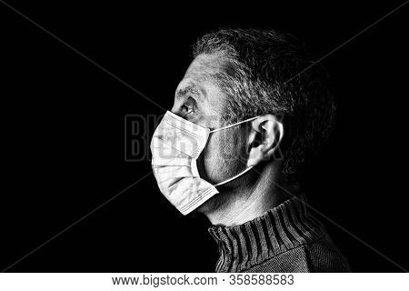 Man with surgical mask. Pandemic or epidemic and scary, fear or danger concept. Protection for biohazard like COVID-19 aka Coronavirus. Profile portrait. Black Background. Black and White.