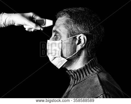 man having the fever measured or taken with digital thermometer by nurse. Pandemic or epidemic, scary, fear or danger concept. Protection for biohazard like COVID-19 aka Coronavirus. Black and White