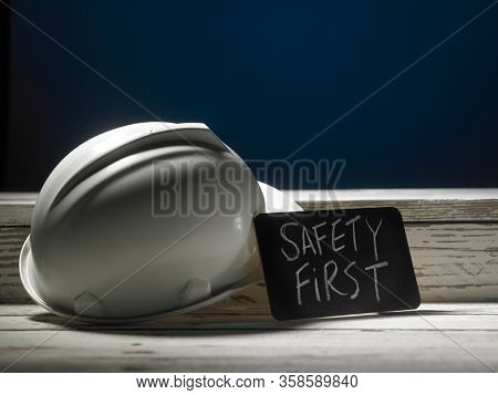 Safety first concept white hard safety wear helmet hat - Engineer worker helmet on wooden background.