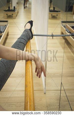 Female Dancer Doing Leg Stretches On The Ballet Barre