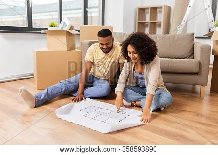 mortgage, people and real estate concept - happy african american couple with boxes and blueprint moving to new home