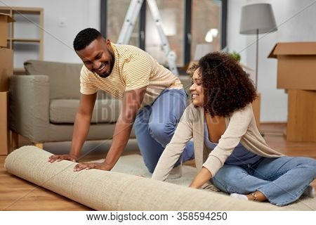 moving, people, repair and real estate concept - happy african american couple with carpet at new home