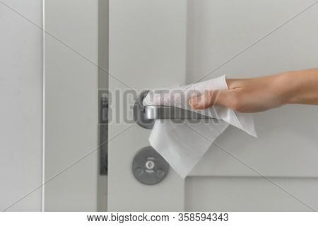 hygiene, health care and safety concept - close up of hand cleaning and disinfecting door handle surface with antiseptic wet wipe