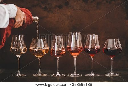 Rose Wine In Glasses And Womans Hand Pouring Wine