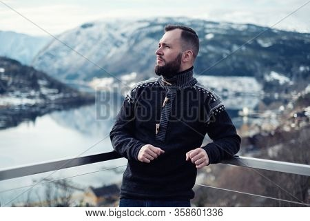 Man looking over Hardangerfjord from house terrace, Norway.