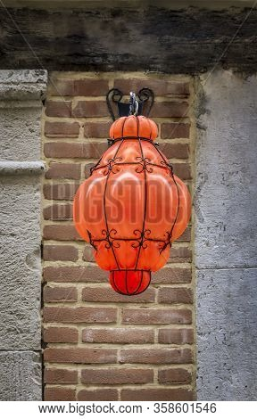 Intricate Bright Orange Blown Murano Glass Street Light Hanging Outside In A Street In Venice, Italy