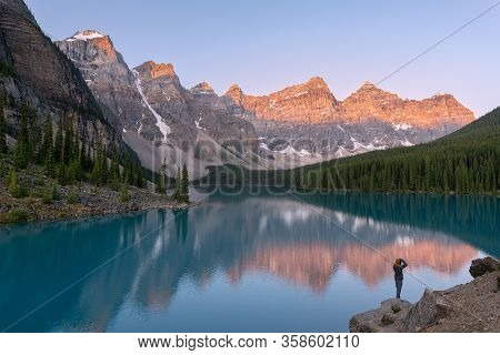 Photographer Capturing Moraine Lake In Banff National Park, Alberta, Canada At Sunrise