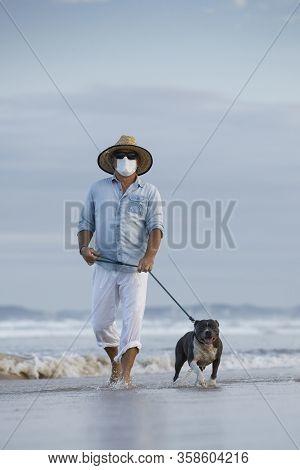 Man With Medical Face Mask Walking A English Blue Staffy Dog Seaside, Mans Best Friend, Walking Dog